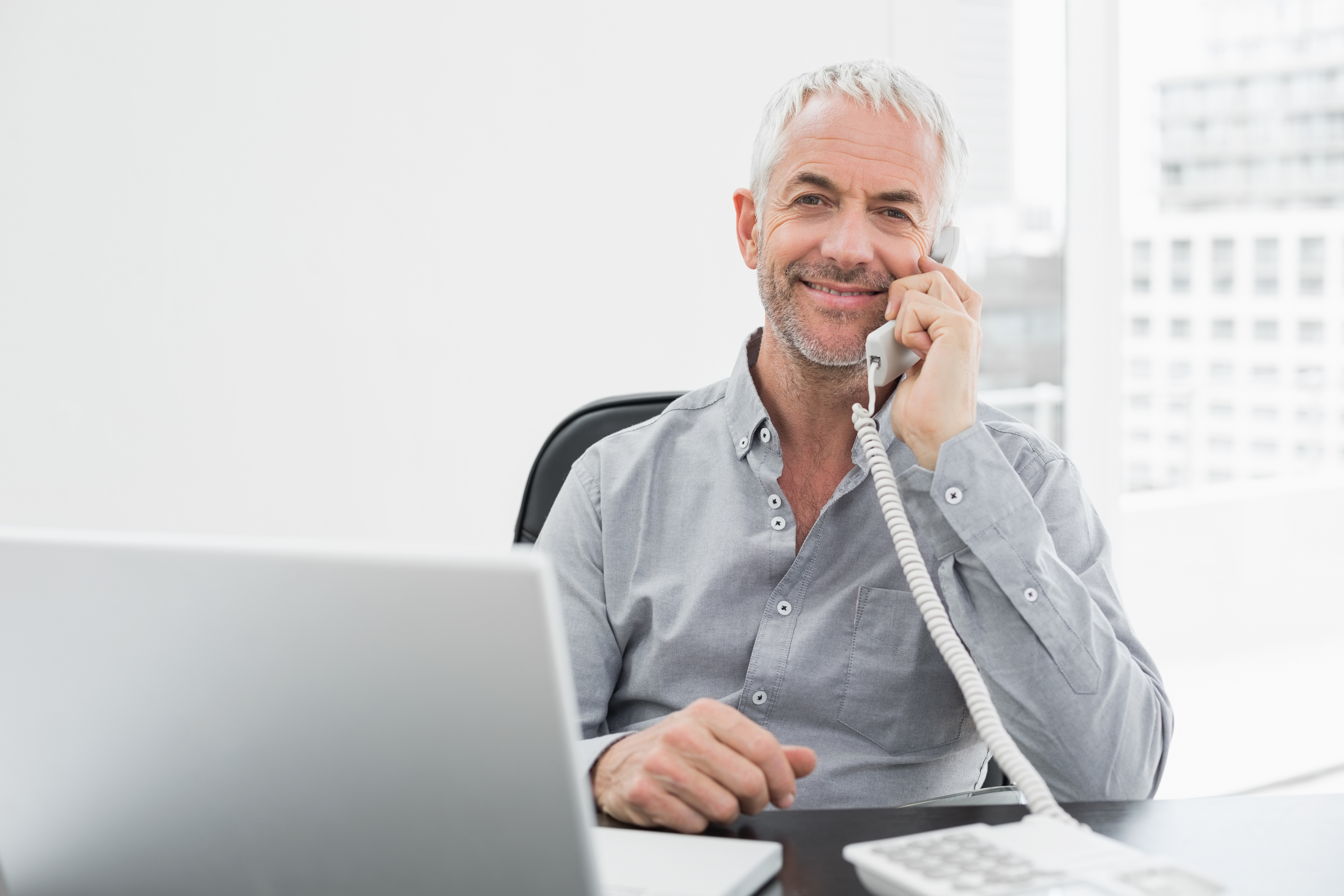 portrait of a smiling mature businessman on call in front